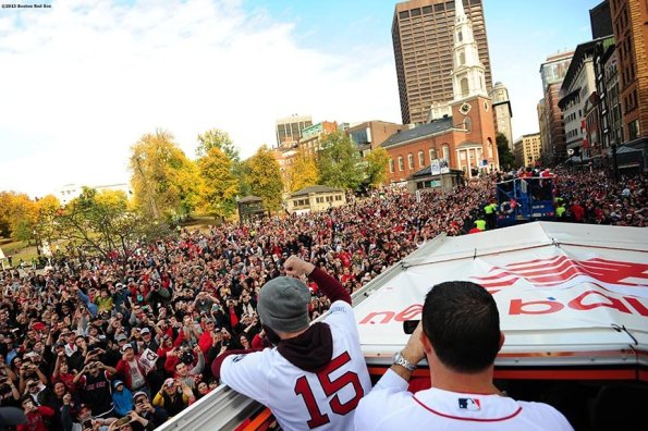 """""""Boston Red Sox second baseman Dustin Pedroia waves to fans during the Rolling Rally World Series Championship Parade through downtown Boston, Massachusetts Saturday, November 2, 2013."""""""