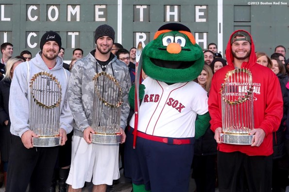 """""""Boston Red Sox pitcher Brandon Workman, catcher Ryan Lavarnway, mascot Wally the Green Monster, and pitcher Drake Britton pose for a photograph with the Olympic Torch and the 2004, 2007, and 2013 World Series trophies during an appearance to Fenway Park in Boston, Massachusetts Thursday, December 12, 2013."""""""