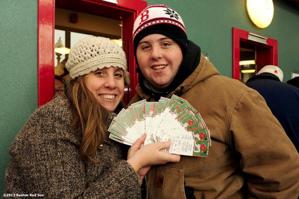 """""""Fans display tickets they purchased for the 2014 Boston Red Sox season during the annual Christmas at Fenway celebration Saturday, December 14, 2013, which featured speaking appearances and autograph sessions with players and coaches, holiday themed attractions and decorations, and opportunities for fans to purchase tickets for the 2014 season."""""""