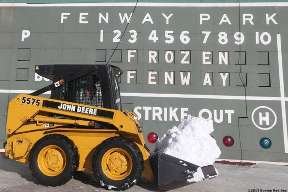 """""""A worker transfers snow in a tractor in front of the Green Monster scoreboard before the first day of Frozen Fenway 2014 at Fenway Park in Boston, Massachusetts Friday, December 27, 2013."""""""