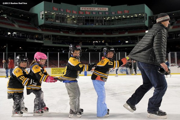 """""""A father leads his children in a lap around the rink at Fenway Park during a skate-around session with former Boston Bruins player Bobby Orr at Frozen Fenway Thursday, January 9, 2014 at Fenway Park in Boston, Massachusetts."""""""