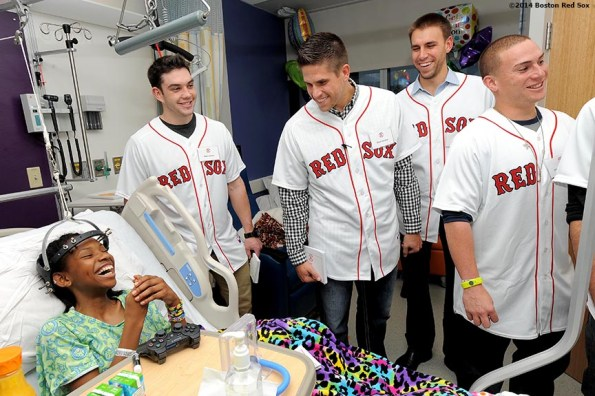 """""""Boston Red Sox rookies (left to right) Blake Swihart, Garin Cecchini, Christian Vazquez, and Matt Barnes laugh as they visit a patient at Boston Children's Hospital in Boston, Massachusetts Wednesday, January 15, 2014."""""""