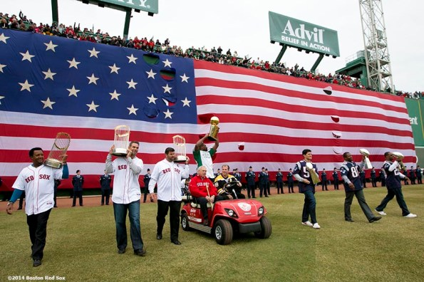 """""""(From left to right) Former Boston Red Sox players Pedro Martinez, Mike Lowell and Jason Varitek, former Mayor of Boston Tom Menino, former Boston Celtics player Leon Powe, former Boston Bruins player Mark Recchi, and former New England Patriots players Tedy Bruschi, Troy Brown, and Ty Law display championship trophies as they are introduced during the Boston Red Sox World Series ring ceremony at the 2014 season home opener Friday, April 4, 2014 at Fenway Park in Boston, Massachusetts."""""""