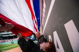 """""""A boy holds an American flag as it is unfurled over the Green Monster during a pre-game ceremony before a game between the Baltimore Orioles and the Boston Red Sox at Fenway Park in Boston, Massachusetts Monday, April 21, 2014."""""""