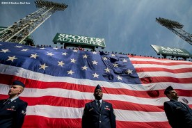 """""""Members of the Hanscom Air Force base stand as an American flag is unfurled over the Green Monster during a pre-game ceremony before a game between the Baltimore Orioles and the Boston Red Sox. """""""