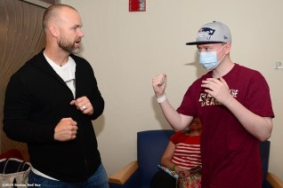 """""""Boston Red Sox catcher David Ross greets a patient during a visit to the Jimmy Fund at the Dana Farber Cancer Institute in Boston, Massachusetts Wednesday, May 21, 2014."""""""