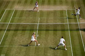 """""""Aisam Qureshi hits a forehand alongside partner Vera Dushevina during a mixed doubles match against Neal Skupski and Naomi Broady at the All England Lawn and Tennis Club in London, England Friday, July 4, 2014 during the 2014 Championships Wimbledon."""""""
