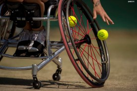 """""""Jordanne Whiley bounces a tennis ball alongside partner Yui Kamiji during a ladies' wheelchair doubles match against Katharina Kruger and Sharon Walraven at the All England Lawn and Tennis Club in London, England Friday, July 4, 2014 during the 2014 Championships Wimbledon."""""""