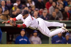 """""""Boston Red Sox third baseman Pablo Sandoval dives to catch a bunt during the fourth inning of a game against the Toronto Blue Jays at Fenway Park in Massachusetts Monday, April 27, 2015."""""""