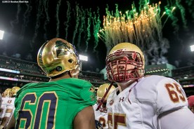 """""""Members of Notre Dame and Boston College shake hands as fireworks explode over the facade after the Shamrock Series Football at Fenway game at Fenway Park in Boston, Massachusetts Saturday, November 21, 2015."""""""
