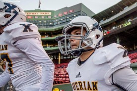 """""""Members of the Xaverian Brothers High School football team take the field before a game against St. John's Preparatory School at Fenway Park in Boston, Massachusetts Wednesday, November 25, 2015."""""""