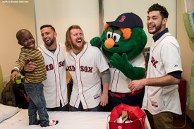 """""""Boston Red Sox infielder Deven Marrero, pitchers Noe Ramirez and Robbie Ross Jr., and mascot Wally the Green Monster laugh as they visit a patient at Dana Farber Cancer Institute during the Holiday Caravan in Boston, Massachusetts Wednesday, December 9, 2015."""""""