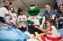 """""""Boston Red Sox infielder Deven Marrero, pitchers Heath Hembree and Robby Scott, and mascot Wally the Green Monster, pitcher Heath Hembree greet a patient during a visit to Shriners Hospital for Children as part of the 2016 Holiday Caravan in Boston, Massachusetts Thursday, December 8, 2016."""""""