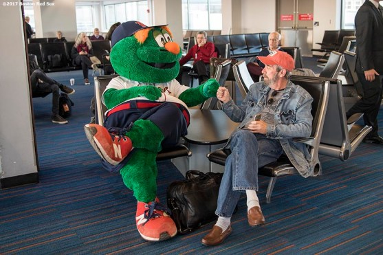 December 13, 2017, Boston, MA: Boston Red Sox mascot Wally the Green Monster greets a passenger during a ticket giveaway to passengers on a jetBlue flight at Logan Airport during The Gift Of Sox in Boston, Massachusetts Wednesday, December 13, 2017. (Photo by Billie Weiss/Boston Red Sox)