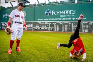 BOSTON, MA - AUGUST 21: Andrew Benintendi #16 of the Boston Red Sox looks on as a Jimmy Fund patient does a cartwheel as she takes the field before a game against the Cleveland Indians on August 21, 2018 at Fenway Park in Boston, Massachusetts. (Photo by Billie Weiss/Boston Red Sox/Getty Images) *** Local Caption *** Andrew Benintendi