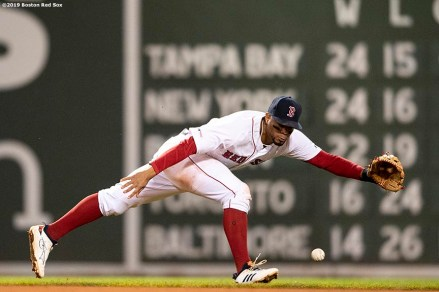 BOSTON, MA - MAY 14: Xander Bogaerts #2 of the Boston Red Sox lunges for a ground ball during the seventh inning of a game against the Colorado Rockies on May 14, 2019 at Fenway Park in Boston, Massachusetts. (Photo by Billie Weiss/Boston Red Sox/Getty Images) *** Local Caption *** Xander Bogaerts