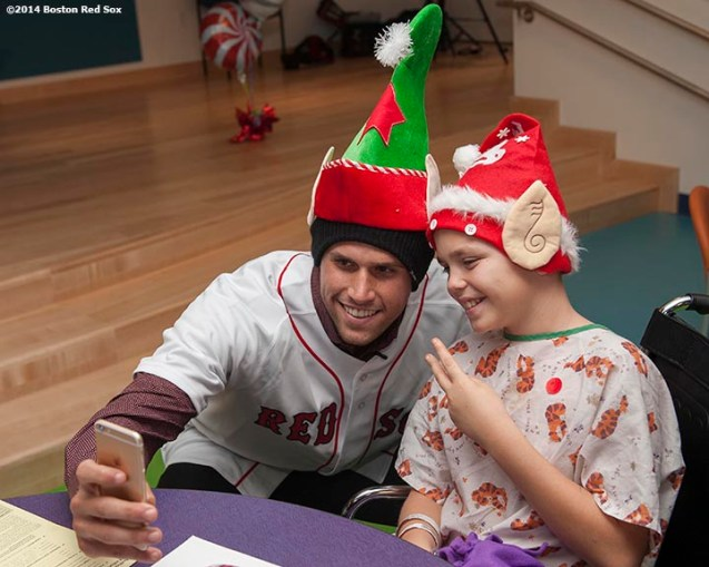 """Boston Red Sox infielder Garin Cecchini poses for a selfie photograph with a patient during a visit to Boston Children's Hospital as part of the Red Sox Holiday Caravan Thursday, December 11, 2014 in Boston, Massachusetts."""