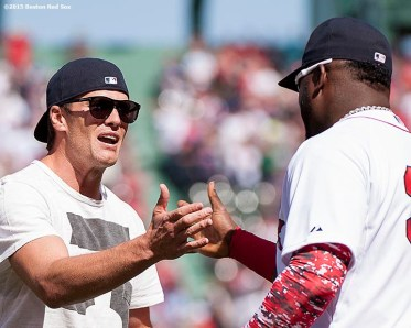 """New England Patriots quarterback Tom Brady reacts with Boston Red Sox designated hitter David Ortiz after throwing out the ceremonial first pitch during a pre-game ceremony before the Boston Red Sox 2015 home opener against the Washington Nationals Monday, April 13, 2015 at Fenway Park in Boston, Massachusetts."""