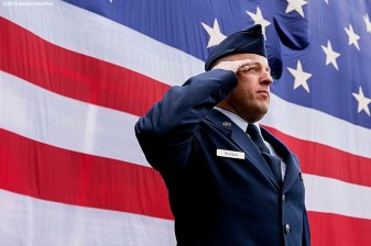 """Senior Master Sergeant Jeff Trudeau of the Hanscom Air Force Base serves as a flag bearer as the American flag is dropped over the Green Monster in honor of Patriot's Day before a game between the Boston Red Sox and the Baltimore Orioles at Fenway Park in Boston, Massachusetts Monday, April 20, 2015."""