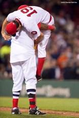 """Boston Red Sox designated hitter David Ortiz picks up pitcher Koji Uehara after defeating theTampa Bay Rays at Fenway Park in Boston, Massachusetts Tuesday, May 5, 2015."""