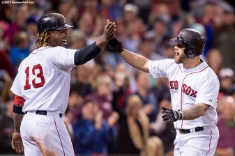 """Boston Red Sox first baseman Mike Napoli high fives left fielder Hanley Ramirez after hitting a two run home run during the sixth inning of a game against the Texas Rangers at Fenway Park in Boston, Massachusetts Saturday, May 23, 2015. It was his second home run of the game."""