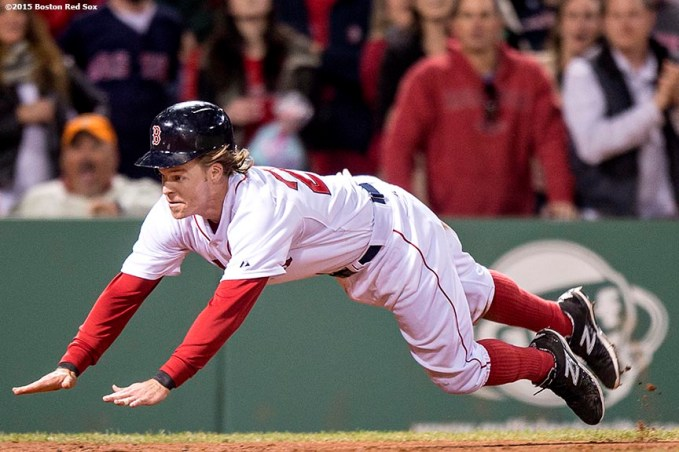 """""""Boston Red Sox third baseman Brock Holt dives into home plate as he scores during the eighth inning of a game against the Texas Rangers at Fenway Park in Boston, Massachusetts Saturday, May 23, 2015."""""""