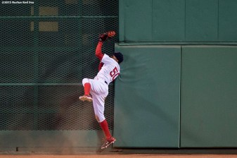 """Boston Red Sox center fielder Mookie Betts high fives fans after scoring during the seventh inning of a game against the Texas Rangers at Fenway Park in Boston, Massachusetts Saturday, May 23, 2015."""