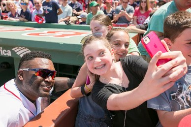 """David Ortiz poses for a selfie photograph with a fan before a game between the Boston Red Sox and the Los Angeles Angels Of Anaheim at Fenway Park in Boston, Massachusetts Sunday, May 24, 2015."""