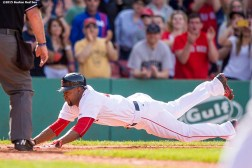 """Boston Red Sox outfielder Alejandro De Aza dives into home plate as he scores during the eighth inning of a game against the Oakland Athletics at Fenway Park in Boston, Massachusetts Sunday, June 7, 2015. It was his first at bat as a member of the Boston Red Sox."""