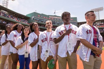 """Members of the Red Sox Scholars program look on from the infield as the National Anthem is sung before a game between the Boston Red Sox and the Oakland Athletics at Fenway Park in Boston, Massachusetts Sunday, June 7, 2015."""