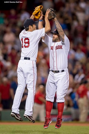 """Boston Red Sox pitcher Koji Uehara and first baseman Mike Napoli high five after a game against the Baltimore Orioles at Fenway Park in Boston, Massachusetts Wednesday, June 24, 2015."""