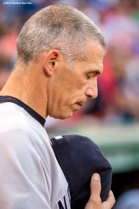"""New York Yankees manager Joe Girardi looks down during the National Anthem before a game against the Boston Red Sox at Fenway Park in Boston, Massachusetts Friday, July 10, 2015."""
