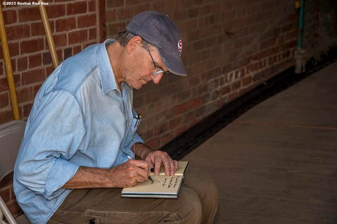 """""""Singer James Taylor writes notes before a concert at Fenway Park in Boston, Massachusetts Thursday, August 6, 2015."""""""