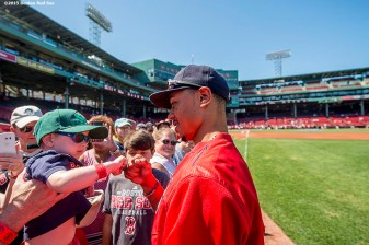"""Boston Red Sox center fielder Mookie Betts fist bumps a young fan during on-field photo day before game against the Philadelphia Phillies at Fenway Park in Boston, Massachusetts Saturday, September 6, 2015."""