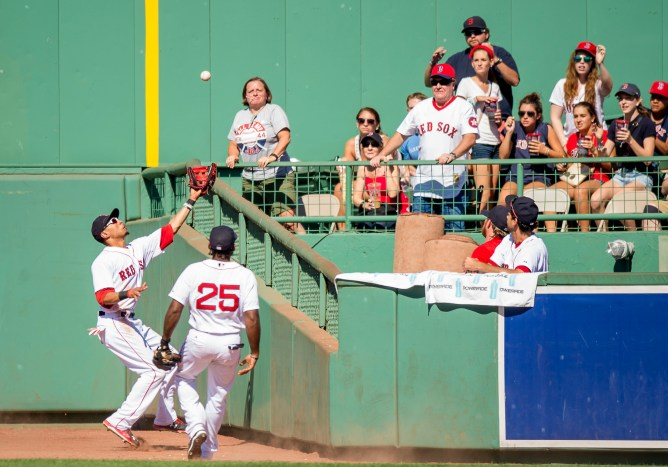 """Boston Red Sox center fielder Mookie Betts catches a fly ball during the fourth inning of a game against the Philadelphia Phillies at Fenway Park in Boston, Massachusetts Sunday, September 6, 2015."""