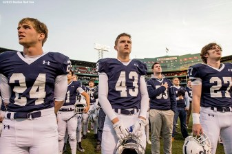 """Members of the St. John's Preparatory School football team look on before a game against Xaverian Brothers High School at Fenway Park in Boston, Massachusetts Wednesday, November 25, 2015."""