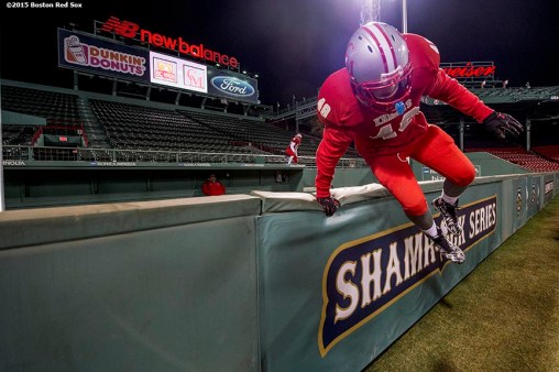 """A member of Catholic Memorial High School jumps over the bullpen wall before a high school football game against Boston College High School at Fenway Park in Boston, Massachusetts Wednesday, November 25, 2015."""