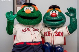 """Boston Red Sox mascot Wally the Green monster poses for a photograph with a statue at Dana Farber Cancer Institute during the Holiday Caravan in Boston, Massachusetts Wednesday, December 9, 2015."""