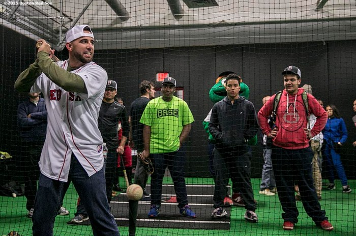 """Boston Red Sox infielder Deven Marrero takes swings in the cage as kids watch at the Base during the Holiday Caravan in Boston, Massachusetts Friday, December 10, 2015."""