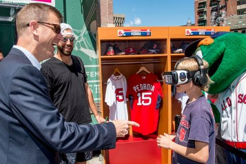 June 15, 2016, Boston, MA: Boston Red Sox President Sam Kennedy and pitcher Matt Barnes interact with a young fan who wears virtual reality goggles during the unveiling of the Red Sox Showcase Mobile Truck powered by T-Mobile at Faneuil Hall in Boston, Massachusetts Wednesday, June 15, 2016. (Photo by Billie Weiss/Boston Red Sox)