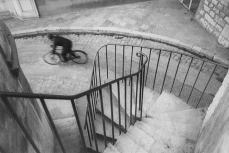 Henri Cartier-Bresson / Magnum Photos. This is a case of seeing the pleasing geometry of the staircase, which roughly equates to the Golden Ratio via the negative space it creates, and waiting for someone to pass through the Phi point the cyclist is in.