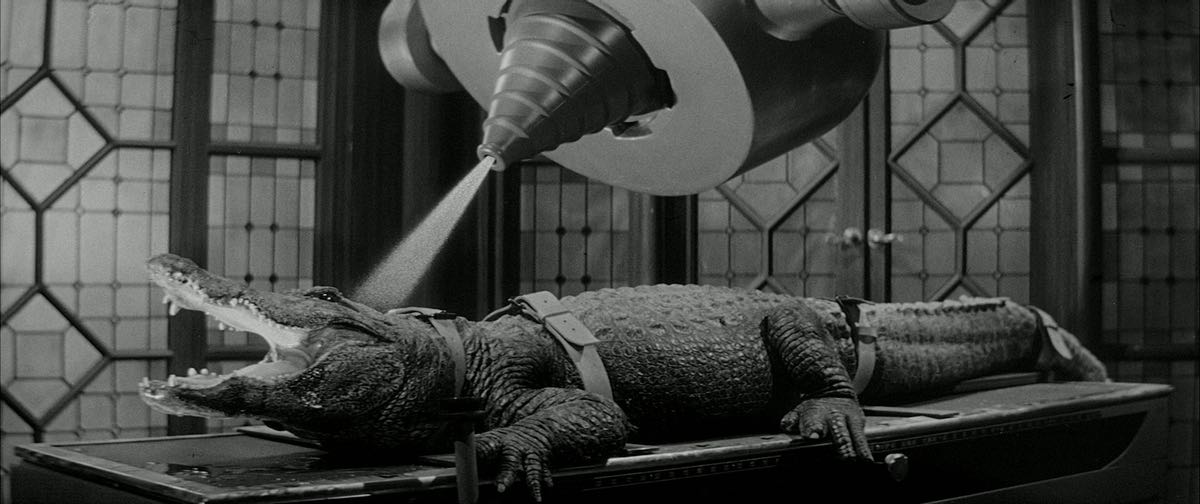 "This is a still from ""The Alligator People"" which shows a damn alligator on an operating table being shot with a laser beam or something."