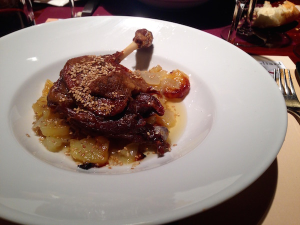 Leg of roast duck with oven cooked potatoes as served as a second plate as part of the menú del día served at Goliard.
