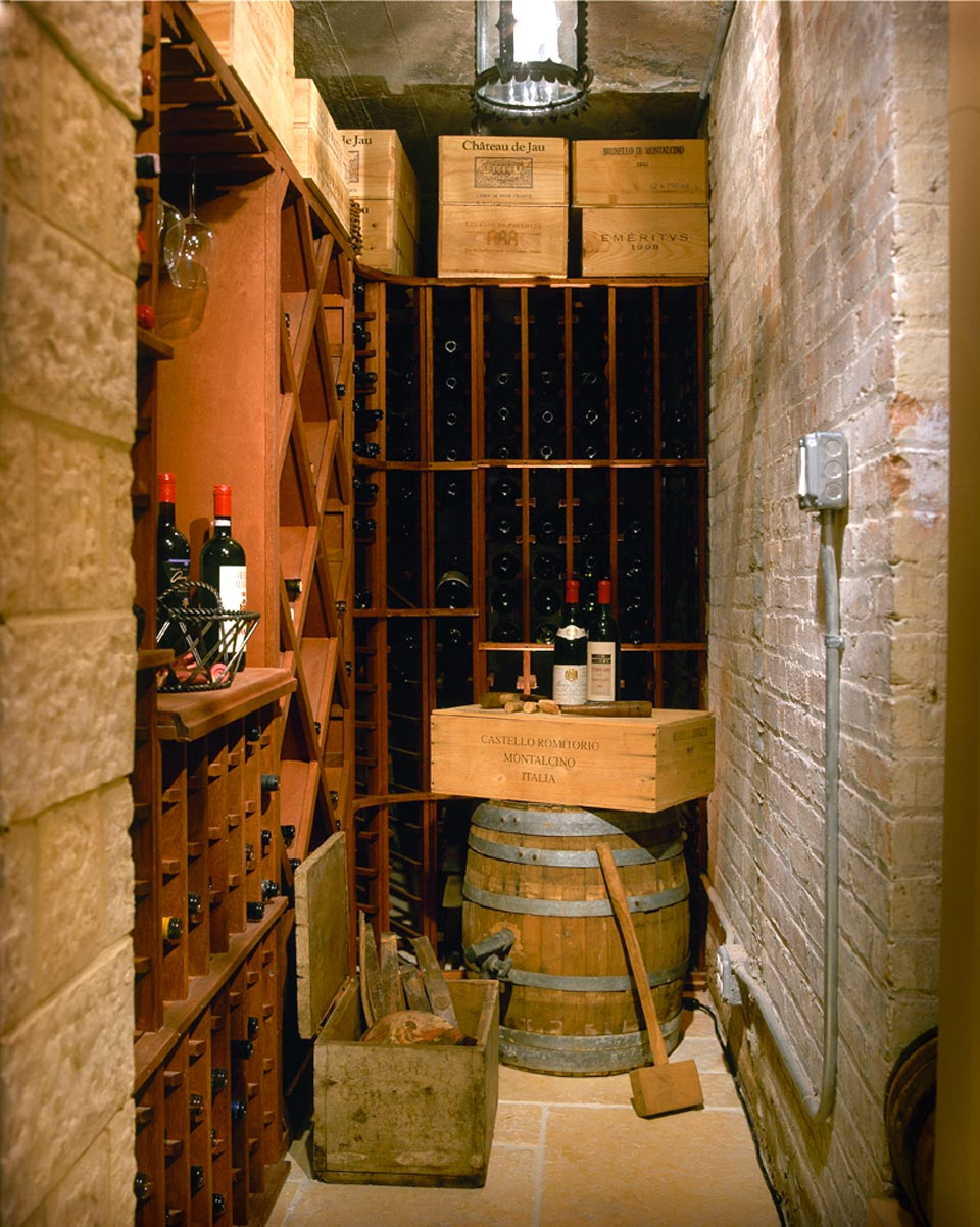 Narrow wine cellar has exposed brick walls and custom built-in wine racks by Bilotta. Design by Regina Bilotta of Bilotta Kitchens.