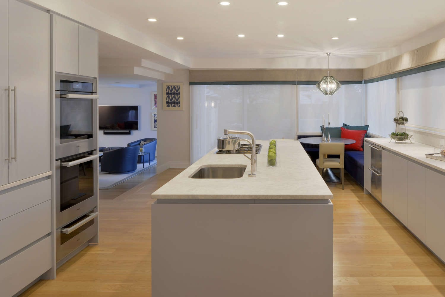 Light contemporary kitchen features a long rectangular island with light quartz countertop and a banquette area. Throught the kitchen there is oak hardwood flooring and fully custom Bilotta cabinetry with channel hardware in flat panel, frameless design painted Benjamin Moore Pigeon Grey. Design by Randy O'Kane, CKD, of Bilotta Kitchens.