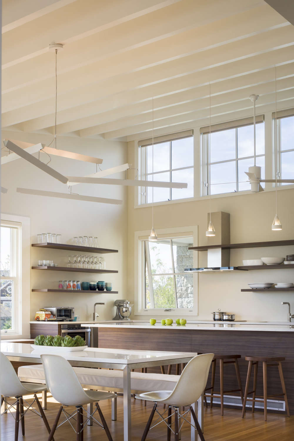 Airy kitchen has high ceilings, abundant natural light and flat panel, fully custom frameless cabinetry by Artcraft in natural walnut. The kitchen features natural walnut open shelving and a large island with white quartz countertop. Design by Randy O'Kane, CKD, of Bilotta Kitchens.