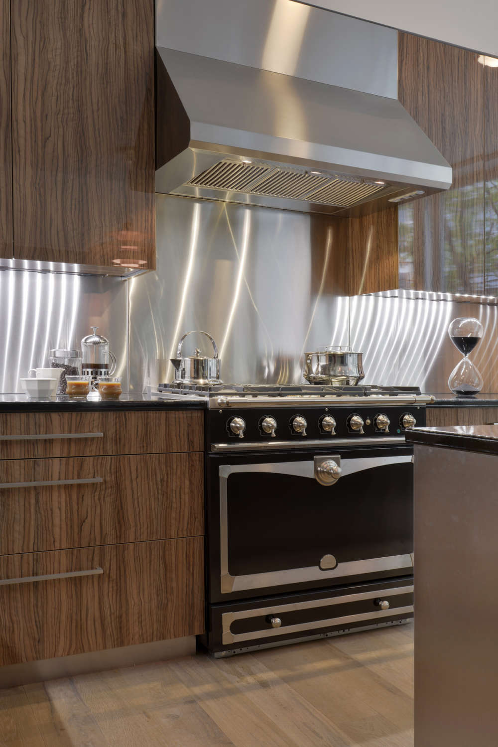 Hearth area of NYC loft kitchen features brushed alumasteel backsplash and flat panel, frameless fully custom Artcraft cabinetry in high gloss olivewood. Design by Randy O'Kane, CKD, of Bilotta Kitchens.