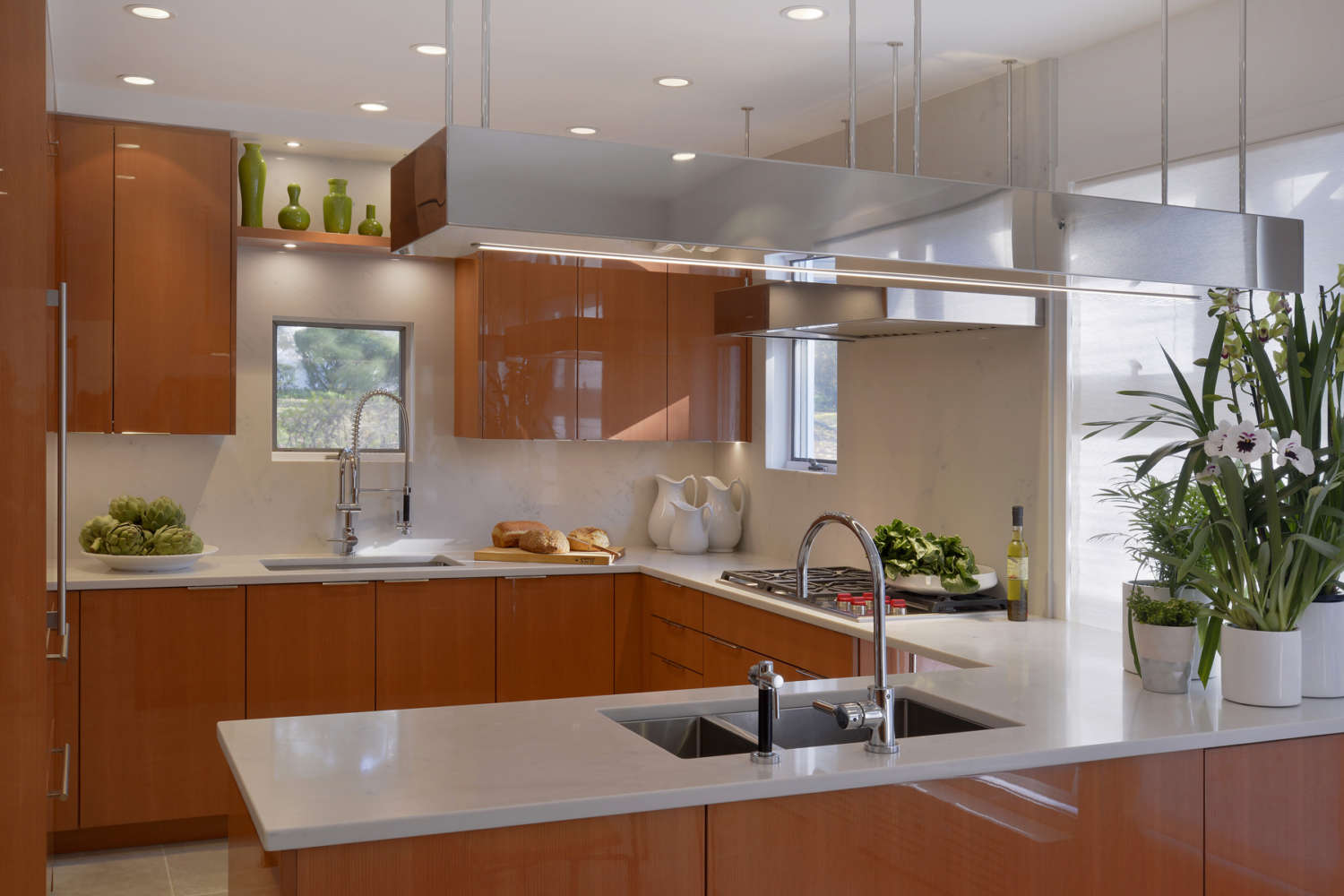 Contemporary kitchen features flat panel, frameless fully custom Artcraft cabinetry in high gloss rift cut cherry, brushed stainless hardware, white quartz countertops, and suspended brushed staineless task lighting. Design by Goran Savic of Bilotta Kitchens.
