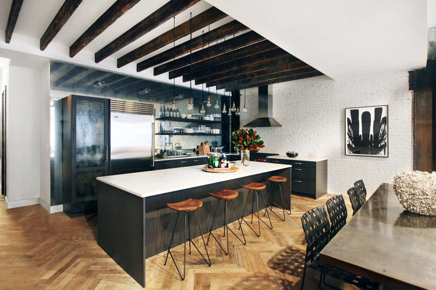 NYC L-shaped loft kitchen features flat panel, frameless fully custom Artcraft cabinetry in smoky oak and open, floating shelving. Large island with seating has a light quartz countertop, and herrigbone oak flooring and whitewashed brick walls adds textural accents. Design by Daniel Popescu of Bilotta Kitchens.