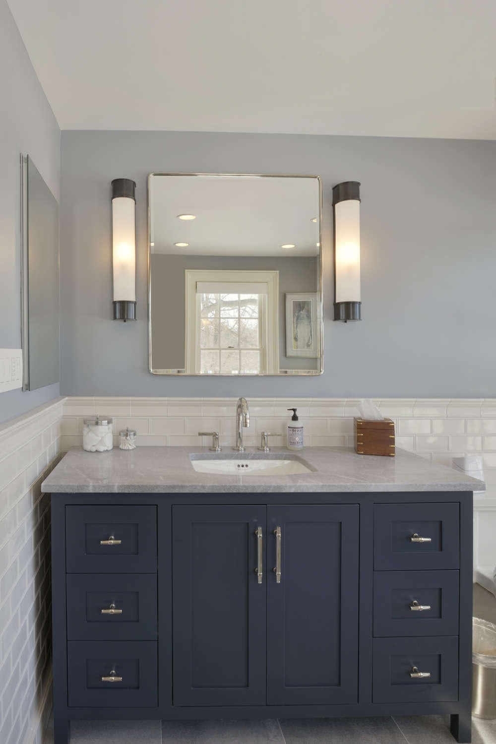 Transitional style master bath features blue painted fully custom vanity by Bilotta Cabinetry with grey marble top with undermount sink, white tiled walls up to the chair rail and light blue painted walls above the chair rail. Design by Paulette Gambacorta of Bilotta Kitchens.